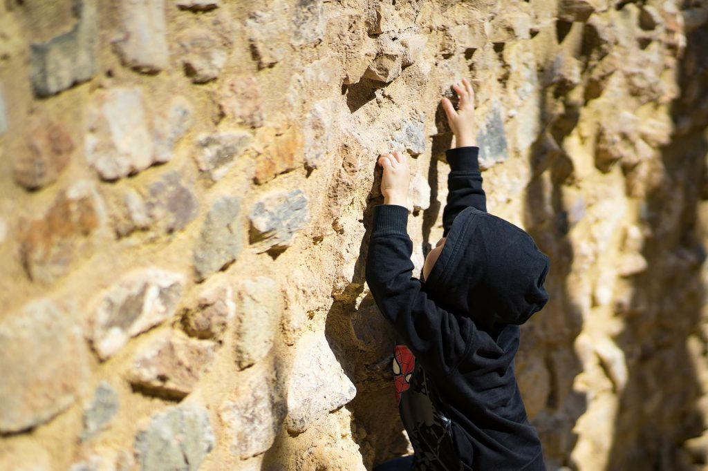 boy climbing on wall