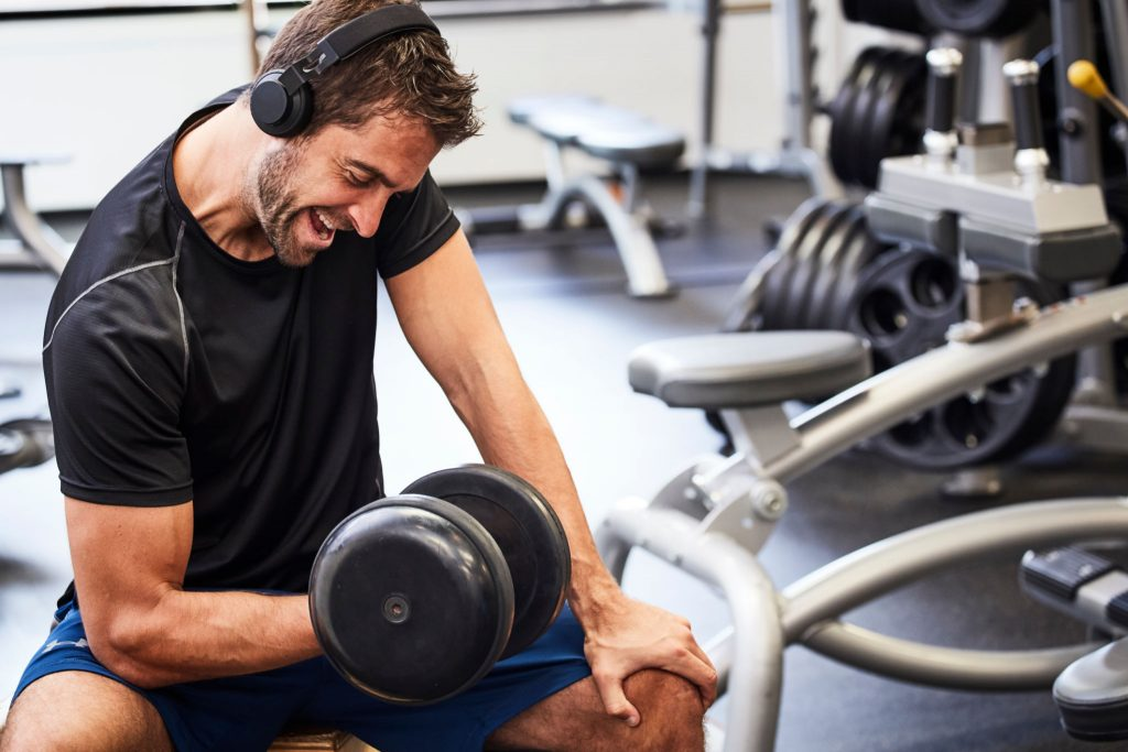 Dude lifting weights while listening to music through sweatproof noise cancelling headphones